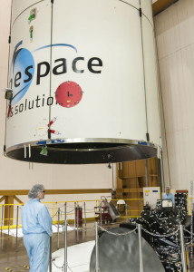 """During integration activity at the Spaceport, the protective fairing containing MEASAT-3b is positioned over Optus 10 – after which it was lowered over the telecommunications satellite to create Ariane 5's dual-payload """"stack."""""""