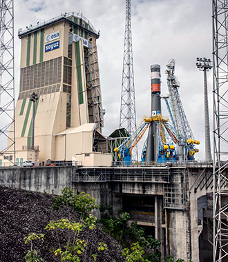 "The Soyuz for Arianespace's Flight VS13 is shown after being suspended over the launch pad by four support arms. At left is the 53-meter-tall mobile gantry, which is moving in to protect Soyuz during the upcoming integration of its ""upper composite."""
