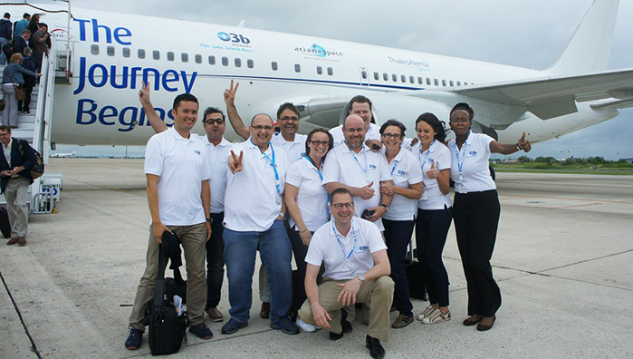 """O3b Networks team members show the company spirit in front of a chartered Boeing 767 that brought executives and guests from Paris to French Guiana for today's VS05 Soyuz mission. This aircraft carried the company's slogan for today's mission: """"The Journey Begins,"""" along with the logos of O3b Networks, Arianespace and Thales Alenia Space."""