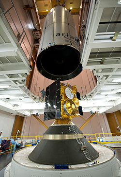 "During integration activity inside the Spaceport's Final Assembly Building for Ariane 5, the payload fairing containing Alphasat is lowered over INSAT-3D to create the launcher's dual-payload ""stack."""