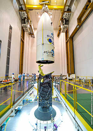 This photo, taken in Spaceport Final Assembly Building's upper level, shows the payload fairing being lowered over EUTELSAT 65 West A, which has been installed on its Ariane 5 launcher.