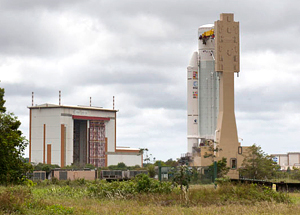 The Ariane 5 for Arianespace's upcoming flight is transferred from the Launcher Integration Building (visible in the background) to the Spaceport's Final Assembly Building for integration of its VINASAT-2 and JCSAT-13 satellite payloads.