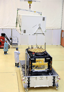 The Galileo FM3 satellite is revealed as the upper section of its protective shipping container is removed in the Spaceport's S1B clean room facility.