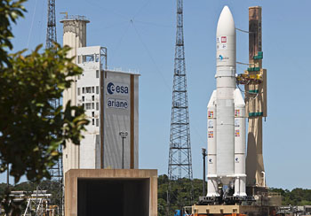 Completing the one-hour transfer process, Arianespace's heavy-lift Ariane 5 approaches its launch pad at the Spaceport under clear French Guiana skies.