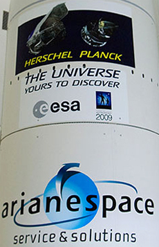 Ariane 5's payload fairing carries depictions of the Herschel and Planck spacecraft and a description of their deep-space mission goal.