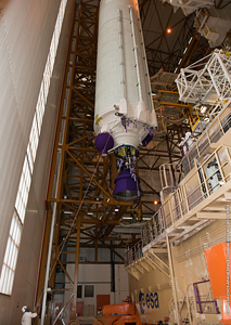 The core cryogenic stage for the fourth Ariane 5 of 2010 is raised for positioning over its mobile launch table inside the Spaceport's Launcher Integration Building.