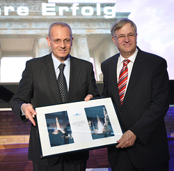 A photo set of Ariane 5 liftoff images for Arianespace missions that orbited Germany's COMSATBw-1 and COMSATBw-2 military communications satellites is presented by Chairman & CEO Jean-Yves Le Gall (at left) to Dr. Peter Hintze, the German Parliamentary State Secretary and coordinator of the federal government's aerospace policy.